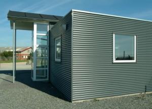 Tagkonstruktionen er ført ud over indgangen, så der er et overdækket område ved døren.